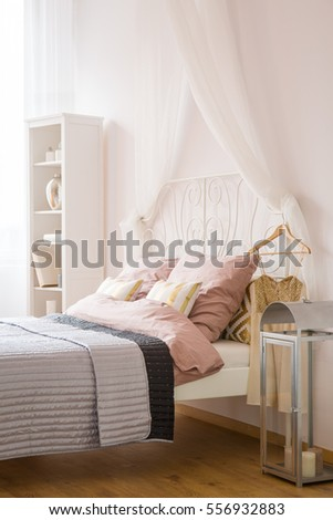 White bedroom with decorative lantern, bed and bookcase