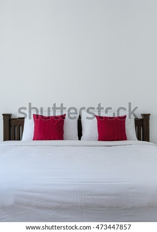 White bedroom with tidy bed and red pillows