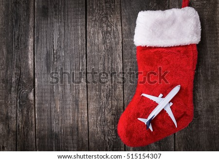 White blank toy of passenger plane on christmas decoration stocking over rustic wooden background. New Year celebration in travel
