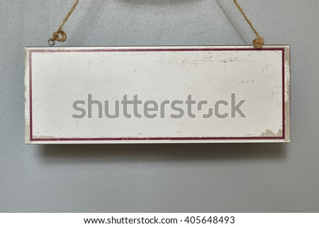 White blank wooden sign hanging on wall supported by strings.