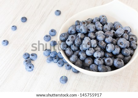 White bowl cup with fresh ripe blueberries  on wooden table