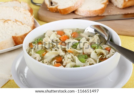 White bowl of chicken and noodle soup