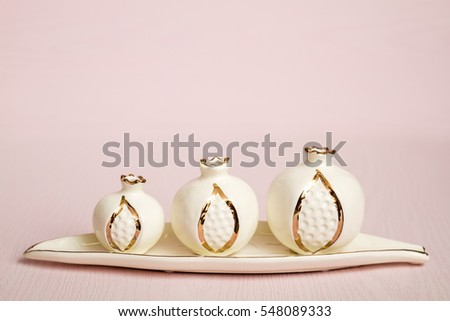 White ceramic pomegranates and white plate on pink background. Organic food, decoration concept.