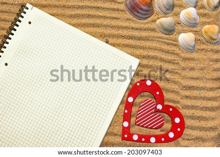 White Checkered Notepad and red wooden heart in beach sand.