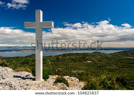White cross against blue sky and fluffy clouds
