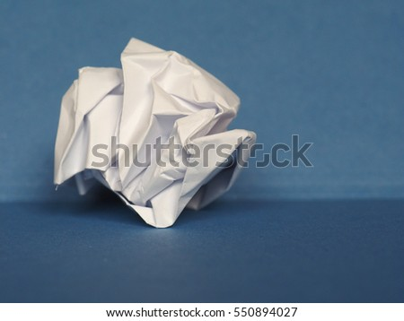 white crumpled paper sheet over blue paper background with copy space