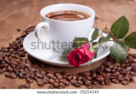White cup of black coffee with coffee beans and red rose