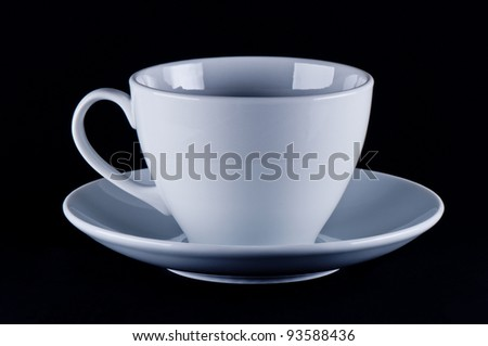 White cup on saucer black background