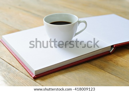 White Cup with coffee standing on the open book in red cover, wooden background.