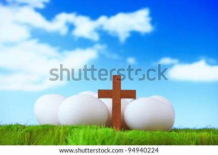 White Eggs And Wood Cross On Grass With Blue Sky Concept For Easter