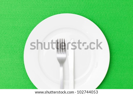 White empty plate with fork and knife on green table cloth