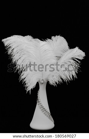 White feathers in vase with silver vintage costume jewelry accents