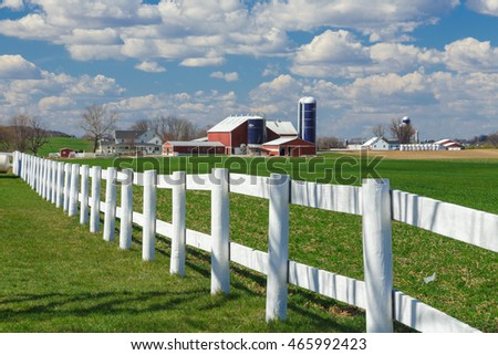 White fence with Amish farm in the distance