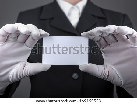 White-gloved hands holding a plastic card