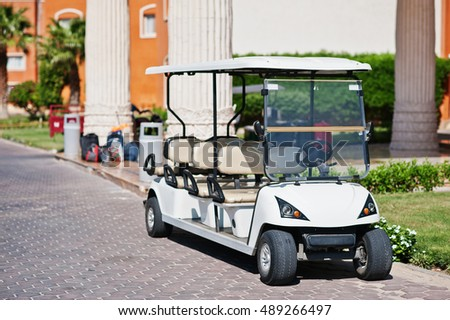 White golf car with back seat on resort.