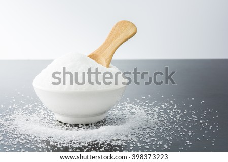 White granulated sugar in white cup with wooden spoon on dark wooden background.