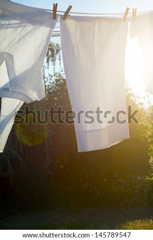 White laundry is drying outside on a sunny summer day