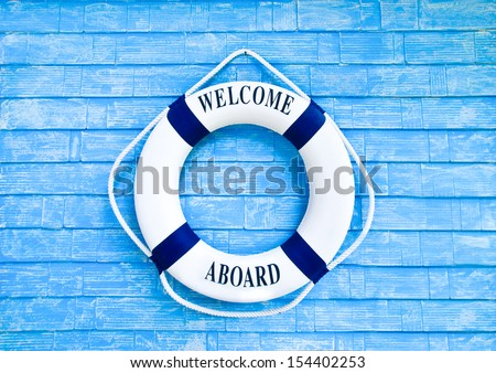 White Life buoy with welcome aboard on blue wall