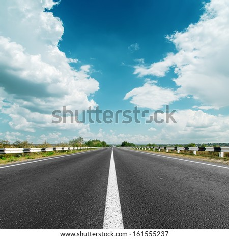 white line on asphalt road and clouds over it