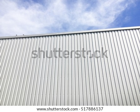 White metal sheet wall of factory and blue sky.