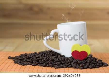 white mug with heart handle and coffee bean on wood background, hot with smoke