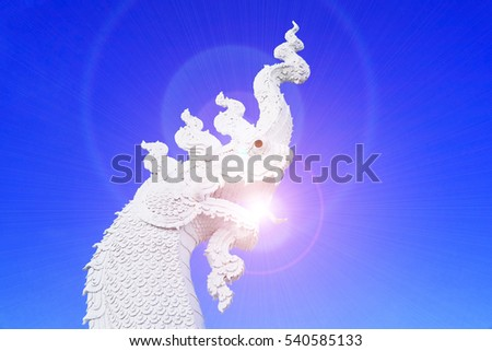 white naga stucco in front of thai temple at Northern Thailand with blue sky background and sun flare effect.