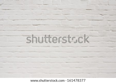 White painted weathered brick wall background. May be used for graffiti