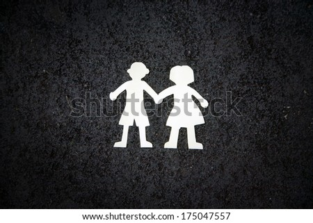 White paper couple silhouettes on the black stone background