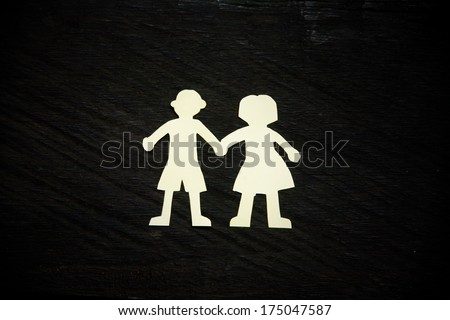 White paper couple silhouettes on the black wooden background