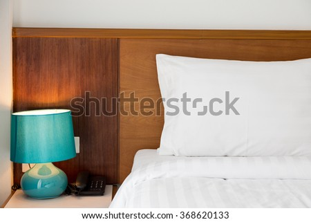 White pillow with telephone and light lamp decoration on bedside in bedroom interior
