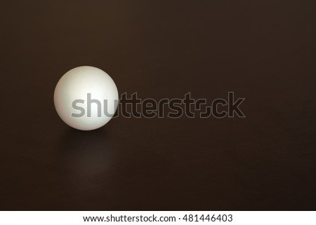 White ping-pong ball on a black desk, reflected.