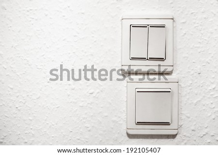 White plastic light switchers on white wallpapered wall