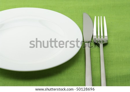 White plate, stainless fork and knife on green linen tablecloth.