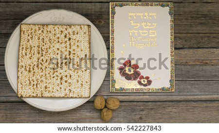 White plate  with matzah or matza and Passover Haggadah on a vintage wood background presented as a Passover seder feast or meal with copy space. Perfect for your Passover design.