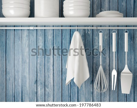 White plates on the shelf, kitchen cooking utensils. Steel spatulas, whisk and towel in front of rustic blue wooden wall.