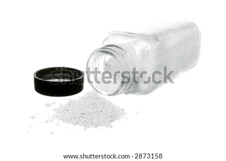 white powder spilling from a clear container on white ground