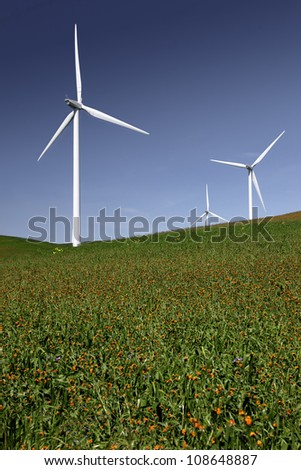 White power generating wind turbines, windmills against  blue sky, on green Spring fields and flowers.
