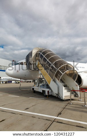 White reactive private jet, front landing gear and gangways