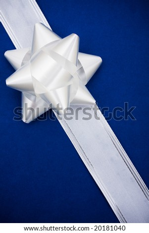 White ribbon and bow on blue background making a present, present