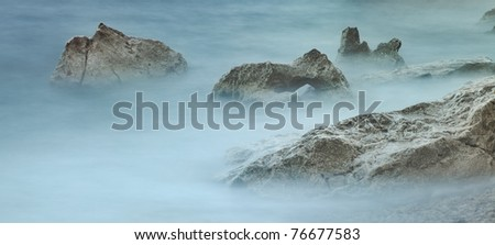 white rocks in misty sea long exposure gives sea water a foggy look peaceful tranquil background scene panorama landscape detail