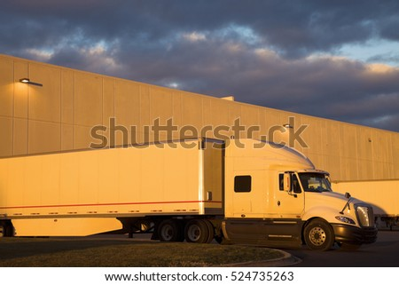 White Semi Truck in the loading dock. Seen during sunset with the warm light and dramatic sky.