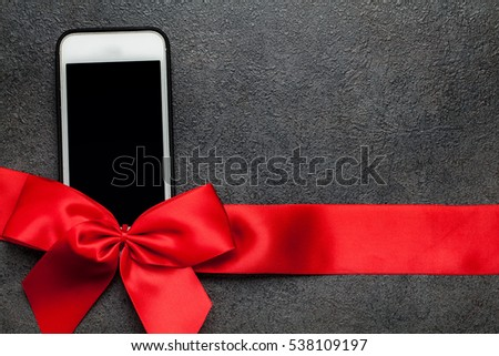 White Smartphone with Red Ribbon and Bow in a black textured background with copy space for free text. Top view.