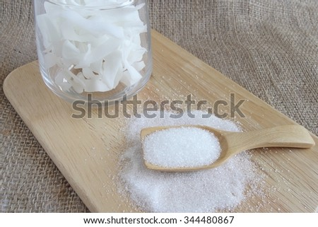 white sugar in wood spoon with candy in glass on wood plate
