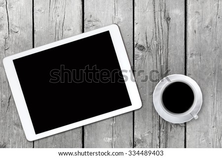 White tablet with a cup of coffee on old wooden desk with boards. Blank screen with space for copy. White old boards as desk.