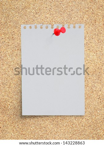 White torn paper note with red pushpin on memo board