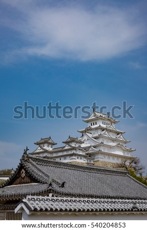 White traditional Japanese castle behind a traditional Japanese building with blue sky and gigantic cloud above
