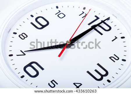 White wall clock with black arrows. Selective focus. Shallow depth of field.