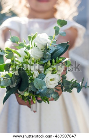 White wedding bouquet holding by white dressed baby girl outdoors