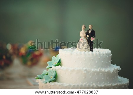 White wedding cake with the small figures of the newlyweds