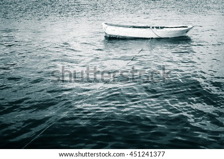 White wooden fishing boat floats on still Sea, blue toned vintage stylized photo